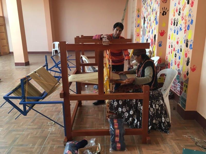 Enseñando el manejo del telar a una participante en el centro de United Change.